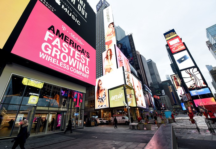 "A T-Mobile billboard in Times Square that reads ""T-Mobile, America's Fastest Growing Wireless Company"""