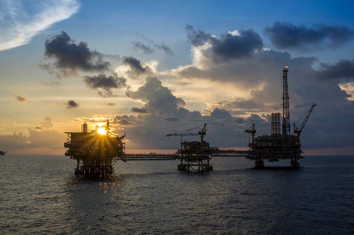 An offshore oil and gas platform at sunset.