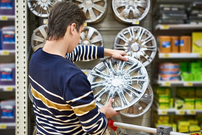 A customer inspects a wheel cap at an auto parts store.