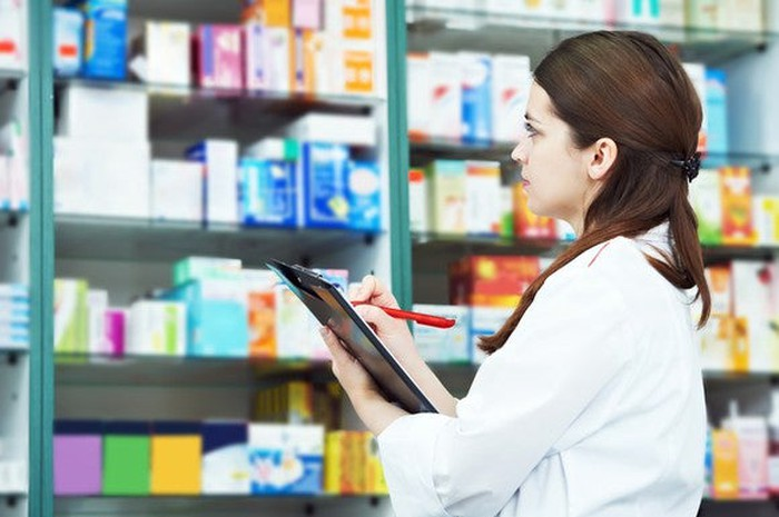 A pharmacist inventories shelves at a retail store.