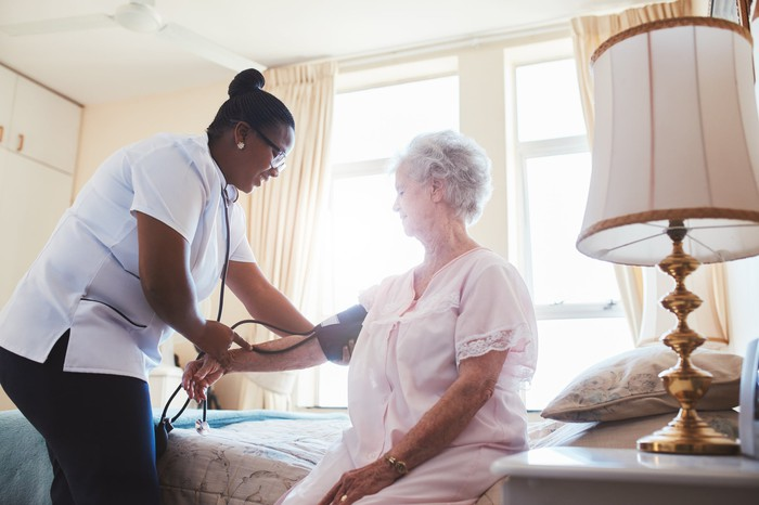 A nurse takes the blood pressure of a senior patent sitting on the edge of a bed.