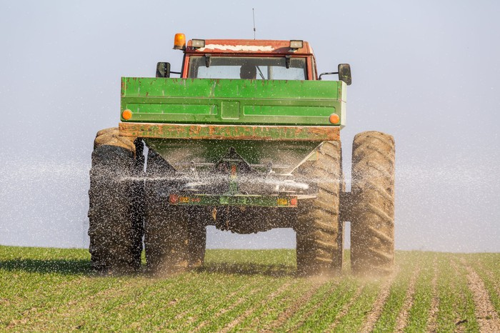 Fertilizer being applied to a field by a tractor.