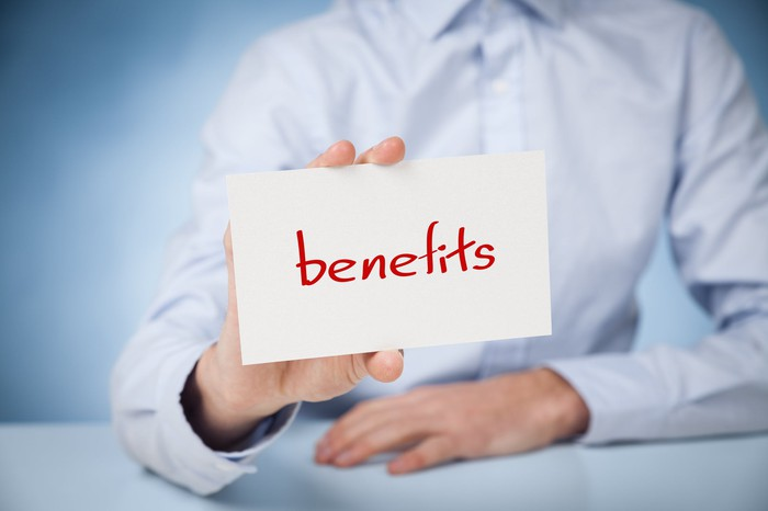 "Person holding a card with the word ""benefits"" written on it"