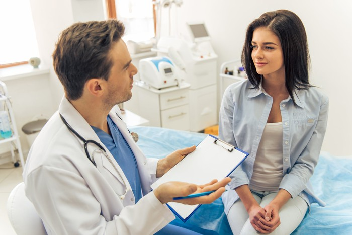 A doctor and a patient sit in discussion in an exam room.