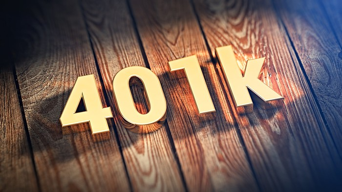 """401k"" in gold block letters on a wooden background"