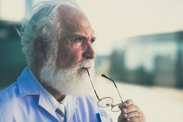 An elderly man thinking while holding part of his glasses between his lips