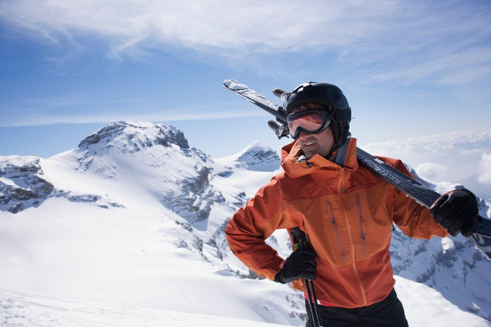 A man holding skis looks out over a snow-covered mountain.