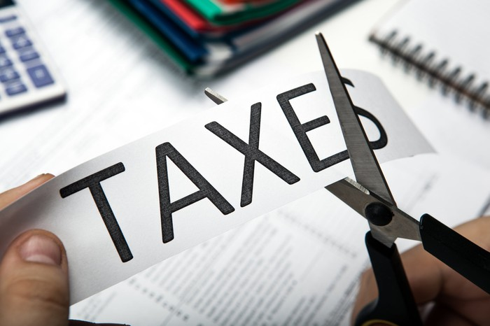 """A pair of scissors cutting the word """"taxes"""" written on a piece of paper."""