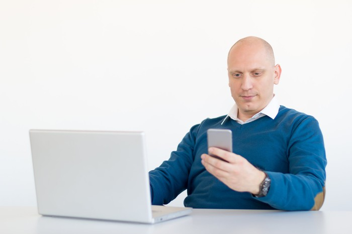 Man checking phone while working on laptop