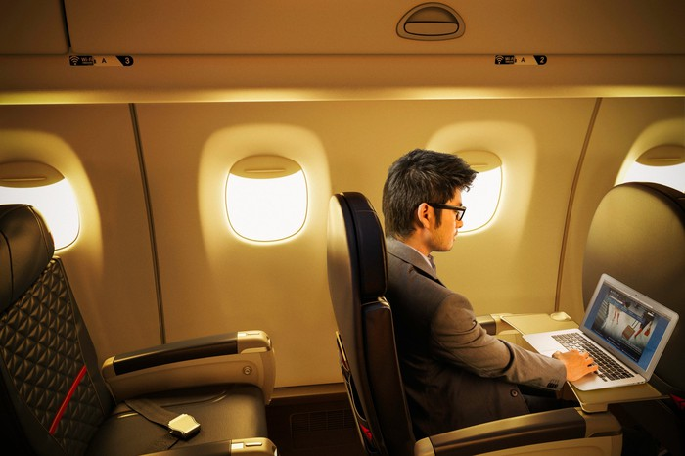 A man using his laptop on a Delta flight.