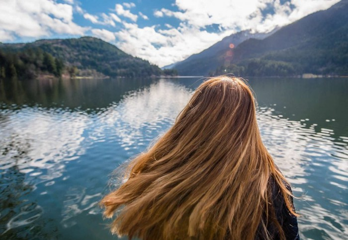 A long-haired woman looking out over a lake.