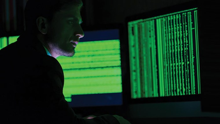 Man sitting in front of a green computer screen