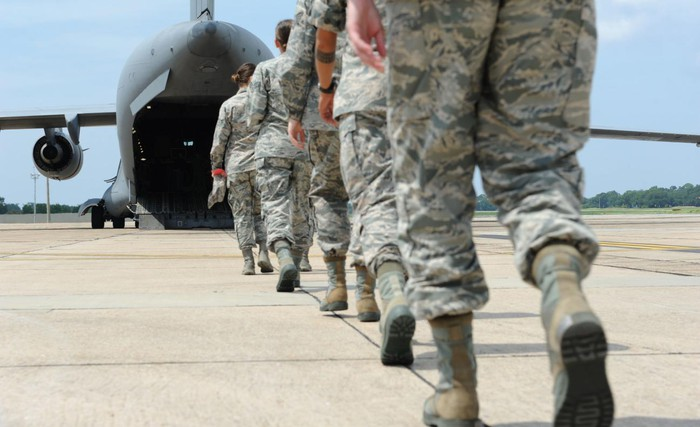 Soldiers walking onto a troop transport plane