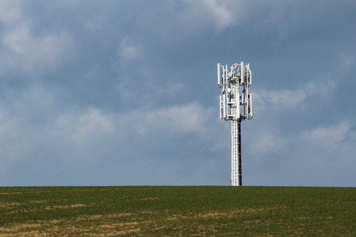 A cellphone tower at the top of a hill with a cloudy sky in the background.