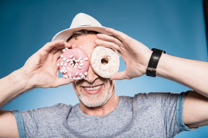 A senior man looking through the holes of two donuts he's holding in his hands.