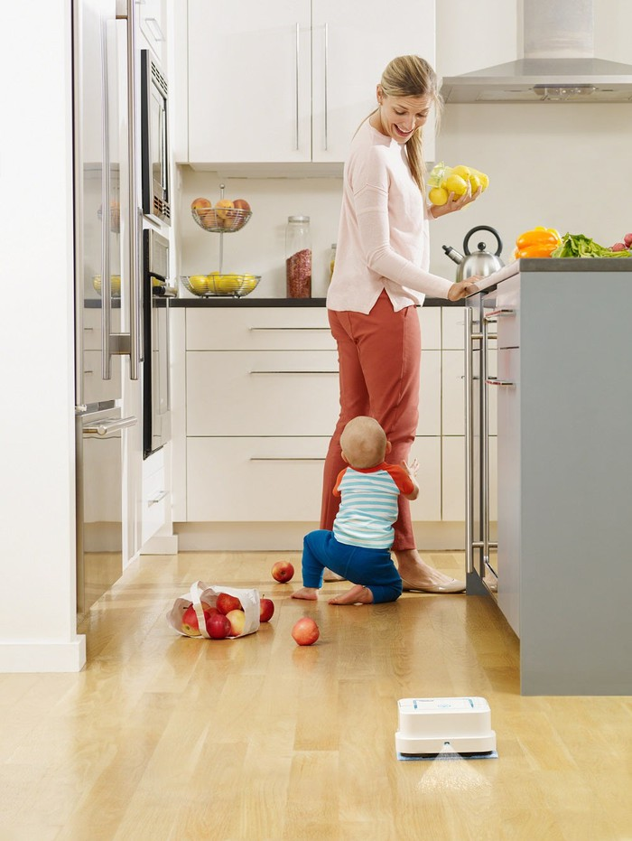 iRobot Braava cleaning a kitchen floor while a mother and child play in the background.