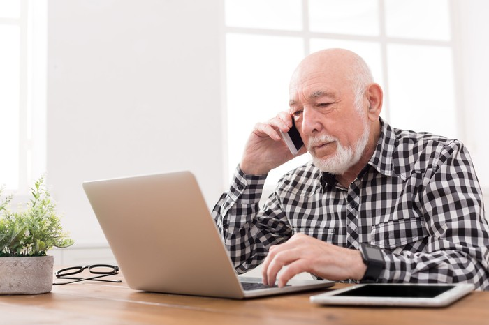 Older man on the phone while typing on a laptop