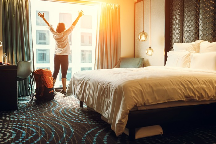 A woman lifts her arms and stretches inside a hotel room
