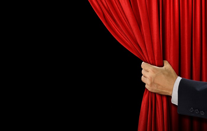 A man's arm pulls back a red curtain to reveal what's behind it.