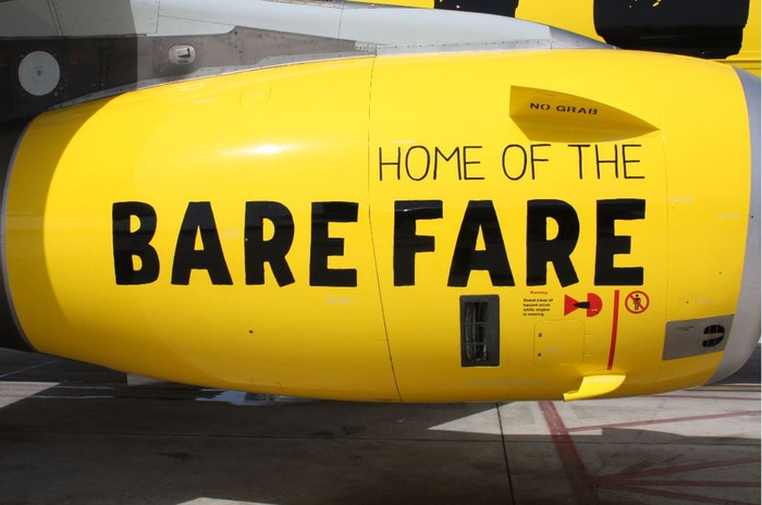 """A Spirit Airline engine that reads """"Home of the Bare Fare"""" on its side."""