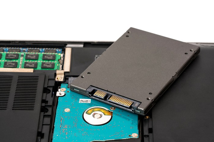 A SSD drive being removed from a laptop.