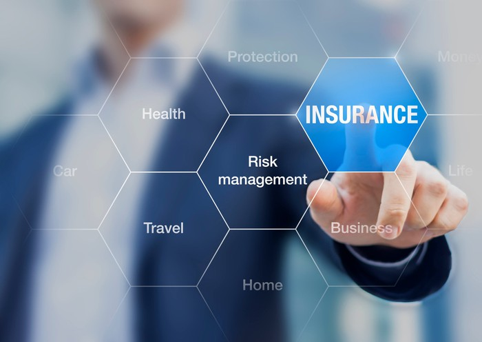 """Businessman pointing toward """"insurance"""" on a screen."""