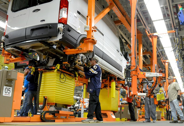 A partially-assembled white Ford Transit van moves down an assembly line at Ford's Kansas City Assembly Plant.