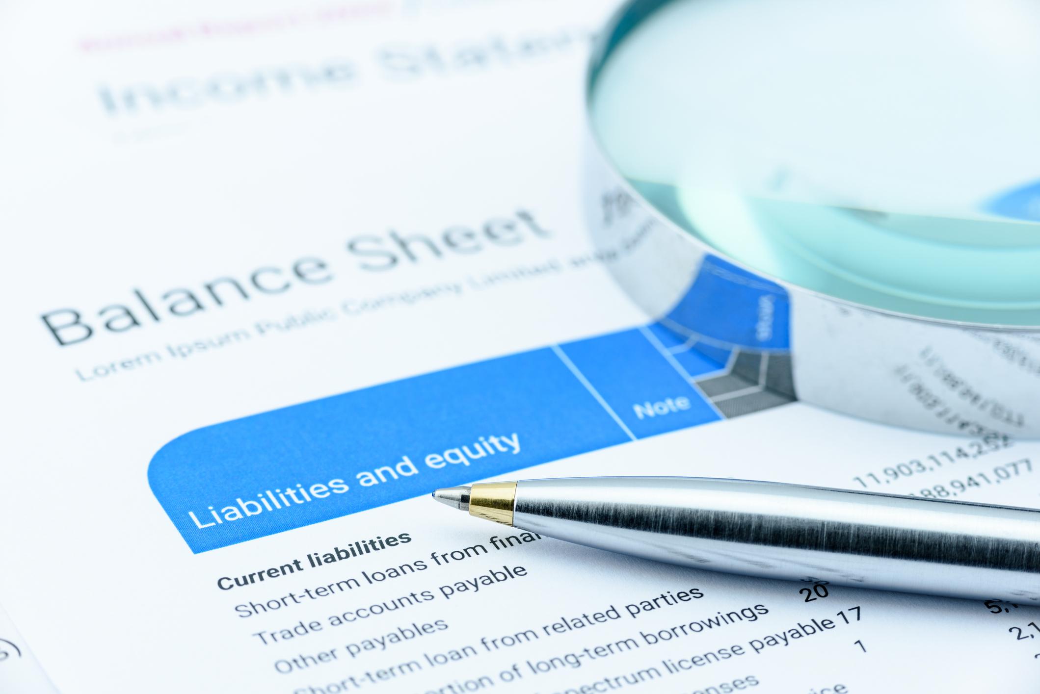 Pen and magnifying glass atop a balance sheet.
