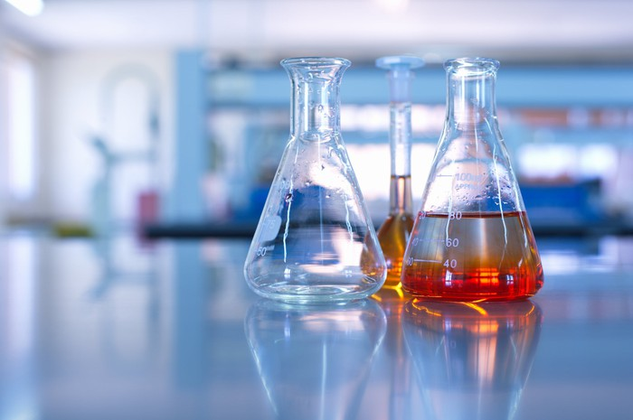 Three glass vessels, one empty and two containing liquids, sit on a table in a lab setting.