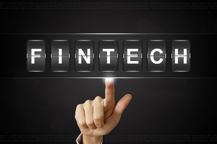 "A person pointing to the word ""FINTECH"""