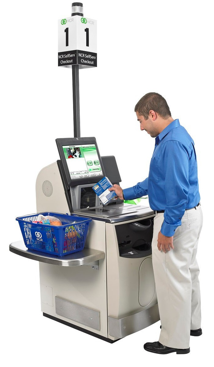 Person scanning groceries at a self-checkout kiosk.