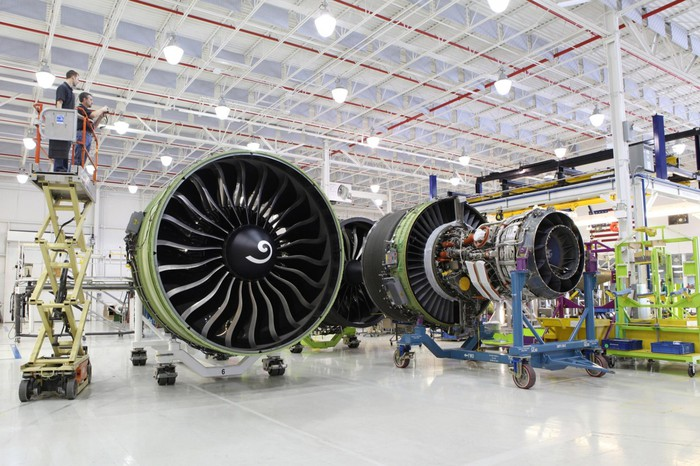 Aircraft engine assembly in a large production facility with workers on risers.