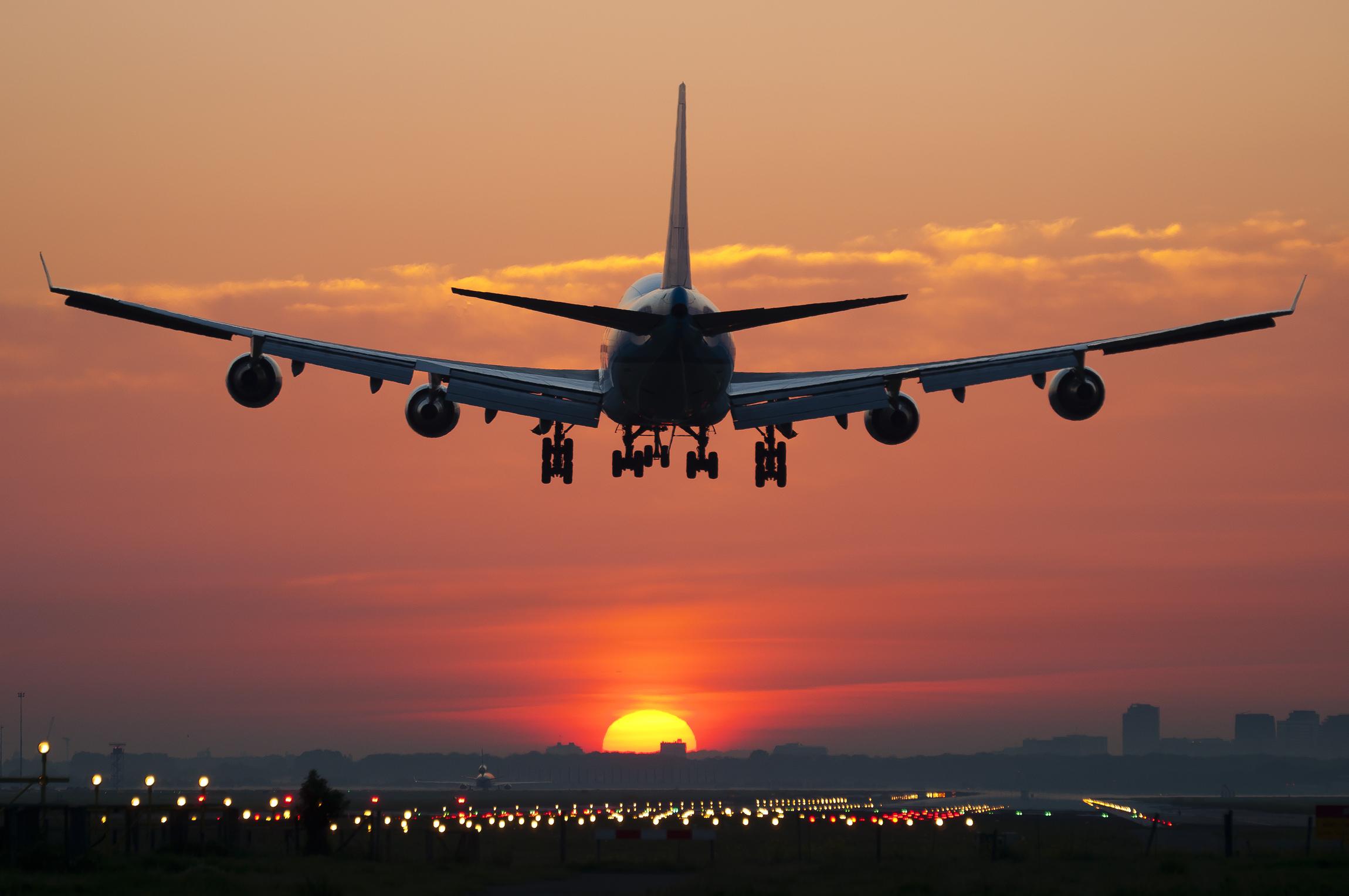 An airplane landing at sunset.