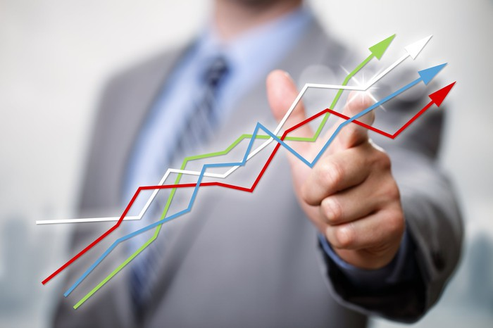 A businessman pointing to line charts going up.