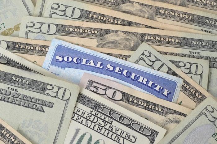 Social Security card nestled among dollar bills