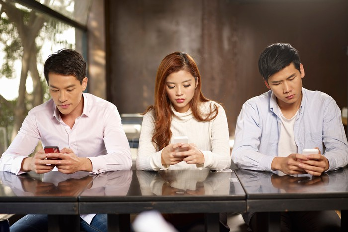 Three young people looking at smartphones, oblivious to each other.