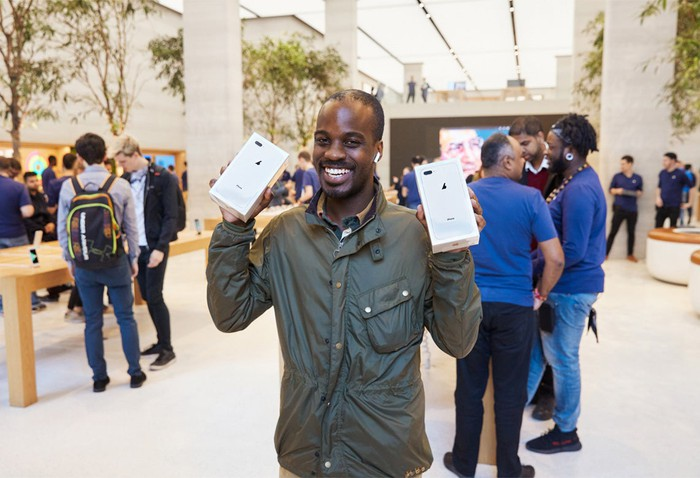 A smiling man holds two iPhone 8 Plus boxes on Apple's iPhone 8 launch day