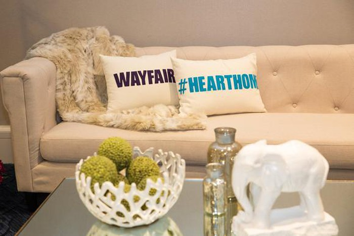 Couch with pillows, one of which has a Wayfair label.