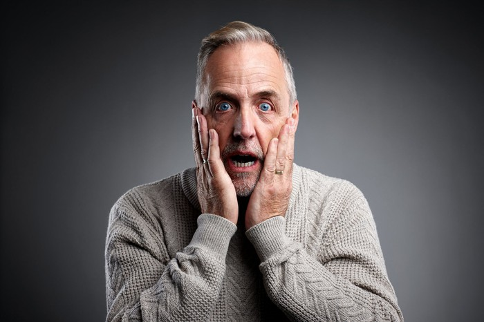 surprised man with hands on his cheeks and his mouth open