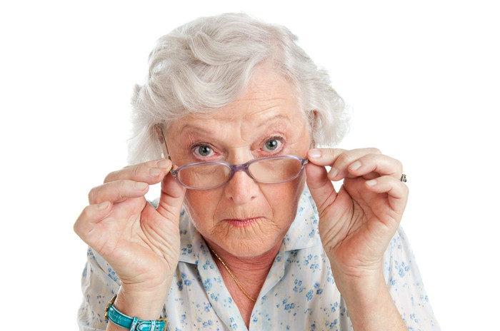 white-haired woman peering with interest over her glasses