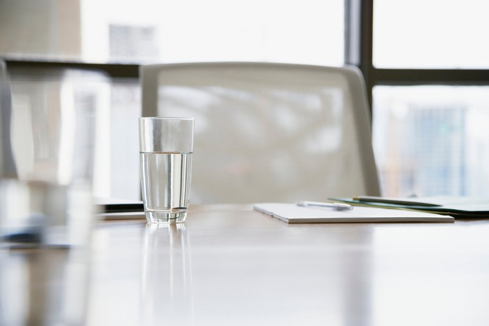 A glass of water sits in front of an empty chair