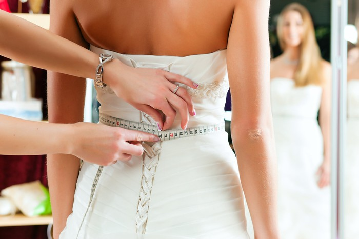 A bride getting her waist measured for her dress