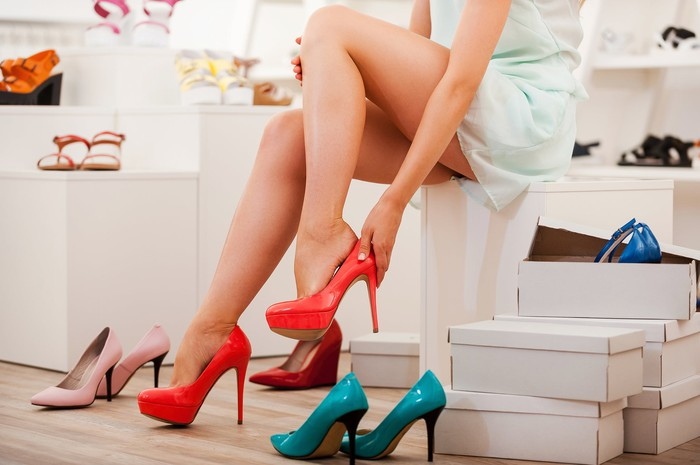 A woman tries on red heels in a store