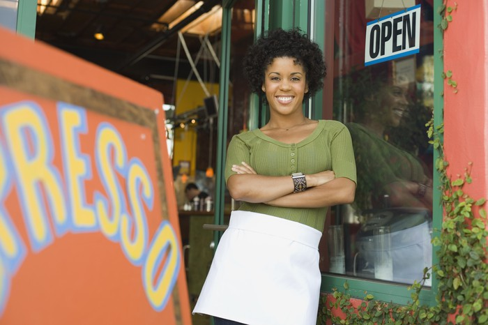 A woman standing outside of her coffee shop