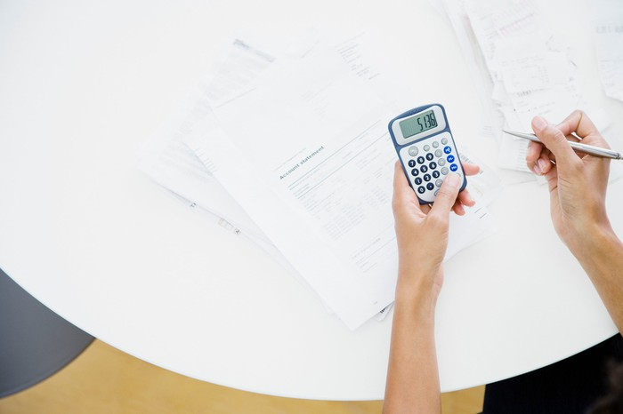 Person sitting at table using a calculator.