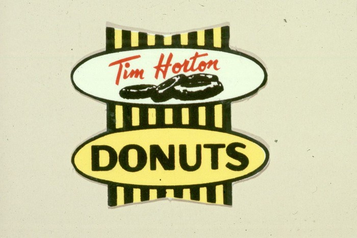 "Original Tim Horton's logo with ""donuts"" written below ""Tim Horton""."