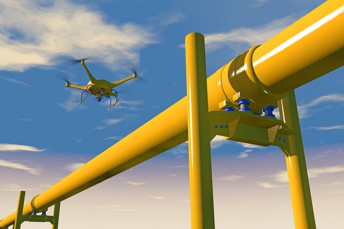 A drone flying over an oil or gas pipeline to inspect it. Blue sky background.