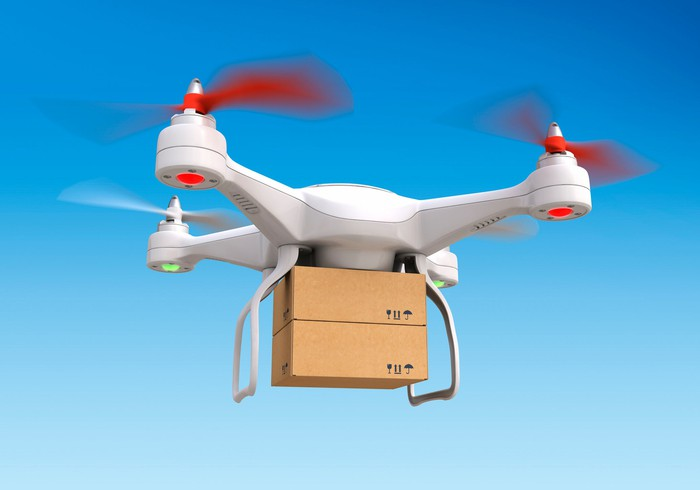 A delivery drone flying in sky carrying two cardboard boxes stacked one atop the other. Blue sky background.
