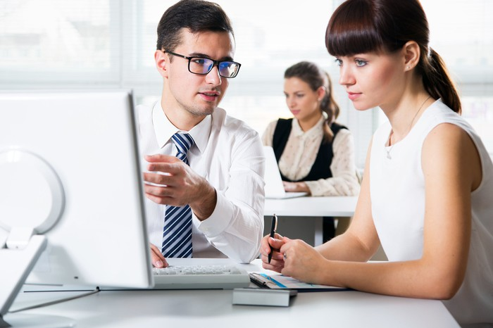 Man showing woman something on his computer screen