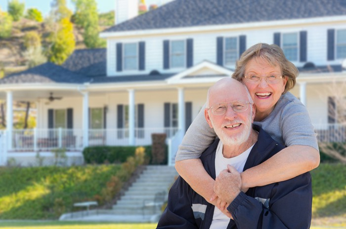Senior couple smiling outside a large house